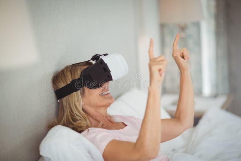 Mujer mayor que usa las auriculares de la realidad virtual imagen de archivo libre de regalías