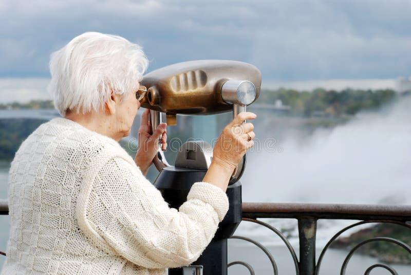 Mujer mayor que usa los prismáticos en Niagara Falls imagen de archivo libre de regalías