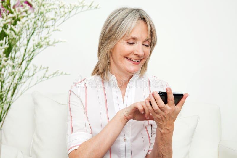 Mujer mayor que usa smartphone imagenes de archivo