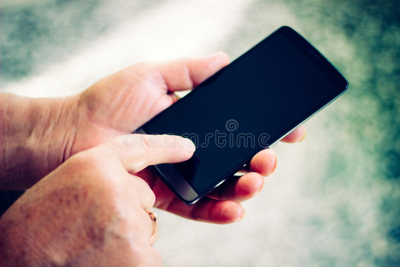 Mujer mayor que usa smartphone fotos de archivo libres de regalías