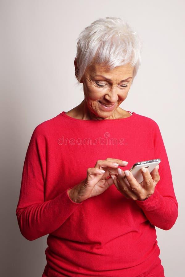 Mujer mayor que usa smartphone imagen de archivo