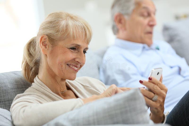 Mujer mayor que usa smartphone en casa imagenes de archivo