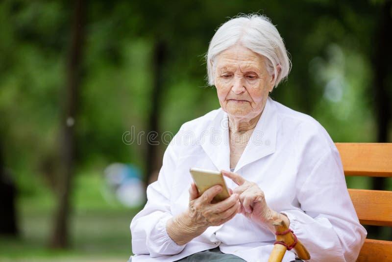 Mujer mayor que usa smartphone mientras que se sienta en banco en parque imagen de archivo libre de regalías