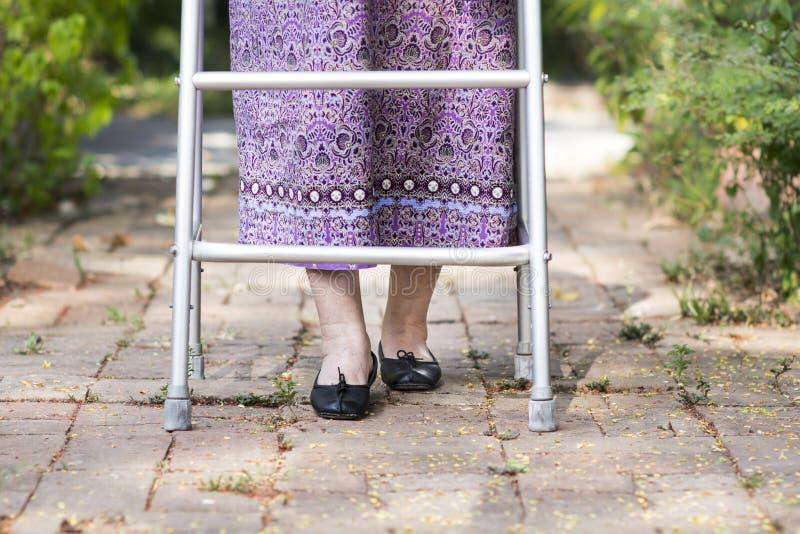 Mujer mayor que usa a un caminante en casa fotografía de archivo