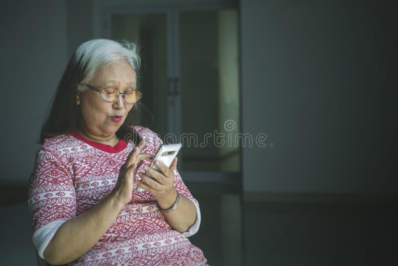 Mujer mayor que usa un teléfono en una silla de ruedas imagen de archivo libre de regalías
