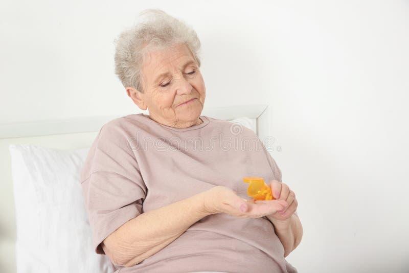 Mujer mayor que va a tomar la medicina mientras que se sienta en cama imagen de archivo