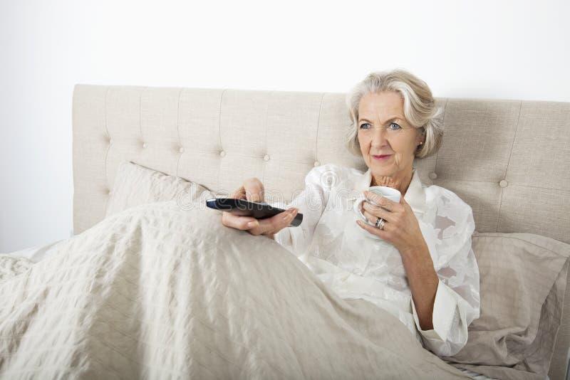Mujer mayor que ve la TV mientras que comiendo café en cama imágenes de archivo libres de regalías