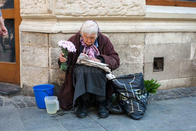 Mujer mayor que vende las flores y leer el periódico en la calle de la ciudad fotos de archivo