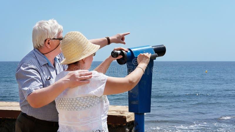 Mujer mayor que viste sombrero, sostiene binocular y hombre que lleva gafas con la mano en el hombro de la mujer y señala al otro fotos de archivo libres de regalías