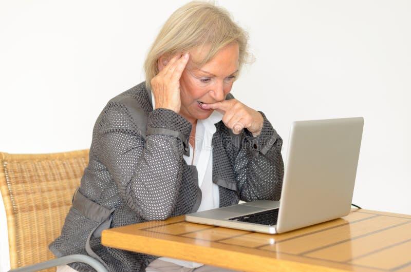 Mujer mayor rubia activa con sentarse formal de la ropa pensativo imágenes de archivo libres de regalías