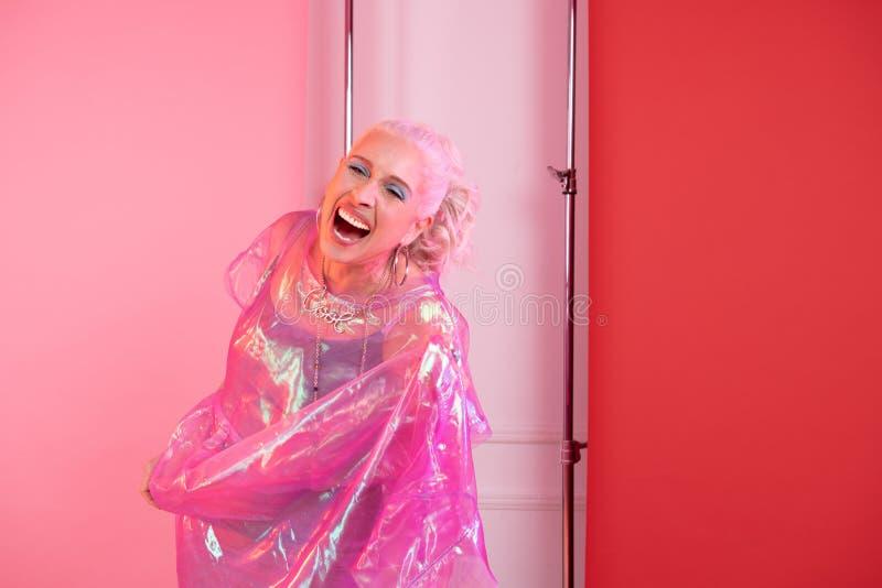 Mujer mayor rubia feliz que ríe durante el tiroteo imagenes de archivo