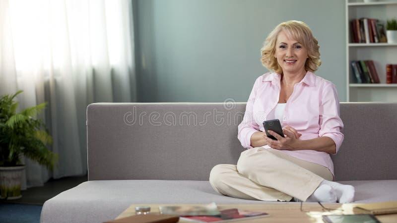 Mujer mayor rubia que sonríe in camera, smartphone de la tenencia, servicio online del app imagenes de archivo