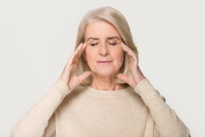 Mujer mayor sana tranquila que da masajes a los templos que sienten alivio de tensión fotografía de archivo