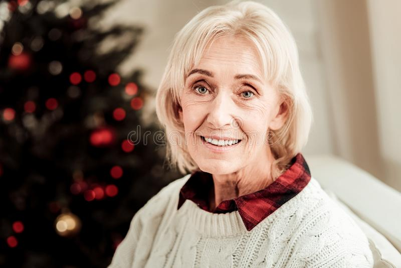 Mujer mayor satisfecha que localiza y que sonríe fotos de archivo libres de regalías