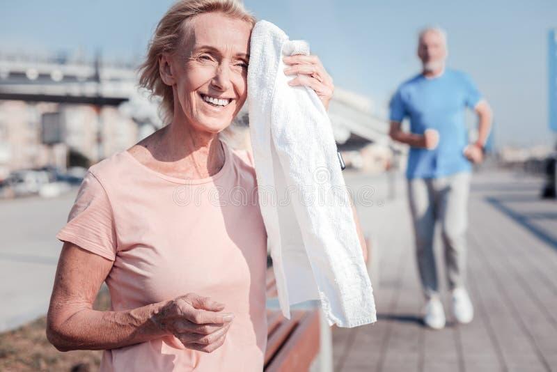 Mujer mayor satisfecha que sonríe y que limpia con una toalla fotos de archivo libres de regalías