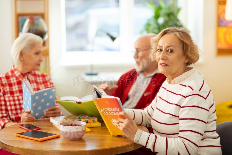 Mujer mayor seria que se sienta en la tabla con el libro imagen de archivo