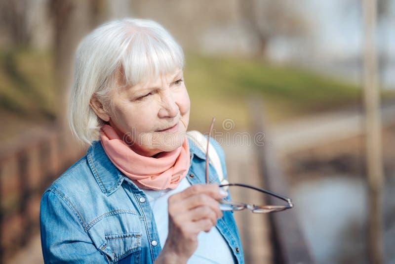 Mujer mayor seria que sostiene sus vidrios fotos de archivo