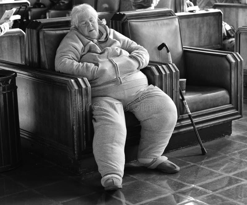 Mujer mayor sin hogar dormida en la estación de tren imagen de archivo