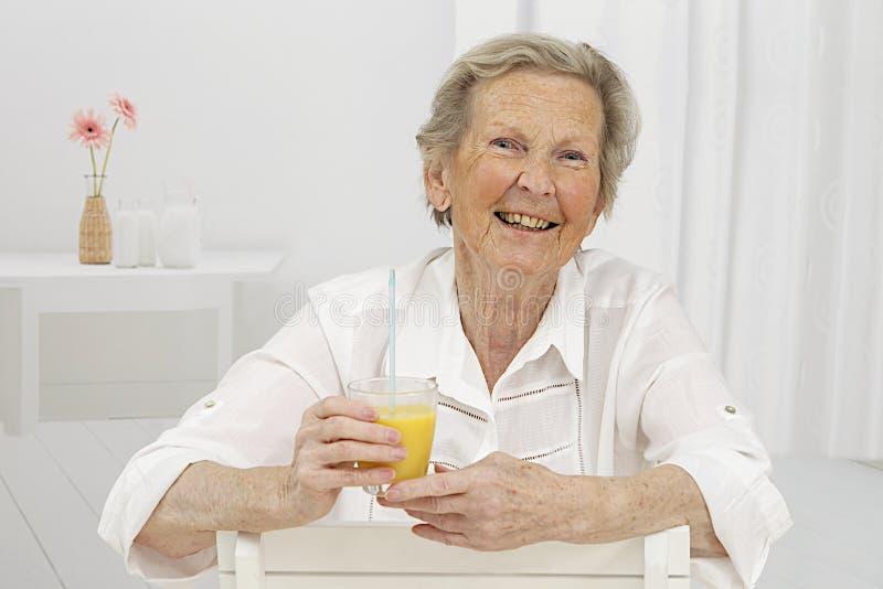 Mujer mayor smilling mientras que bebe el zumo de naranja fotos de archivo libres de regalías
