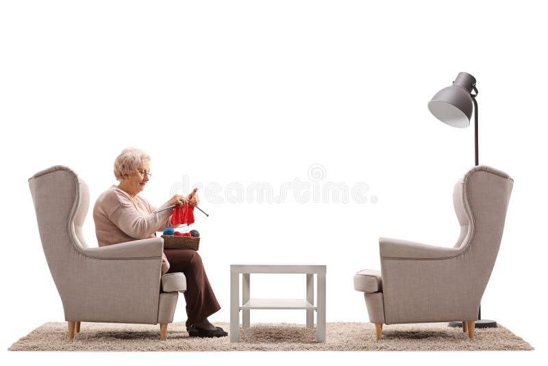 Mujer mayor sola que se sienta en una butaca y hacer punto imagen de archivo