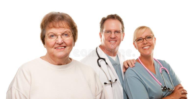 Mujer mayor sonriente con el médico y la enfermera fotografía de archivo libre de regalías