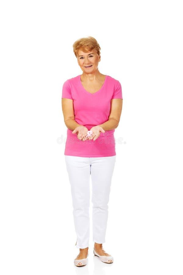 Mujer mayor sonriente con la cinta de la conciencia del cáncer de pecho imagen de archivo libre de regalías