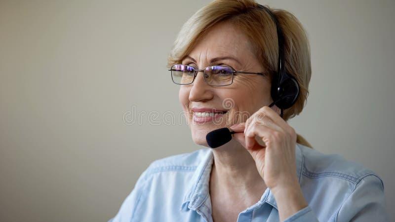 Mujer mayor sonriente con la datación de las auriculares en línea, amor en la edad avanzada, romántica imagen de archivo libre de regalías