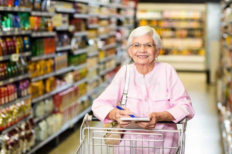 Mujer mayor sonriente con la lista del ultramarinos foto de archivo libre de regalías
