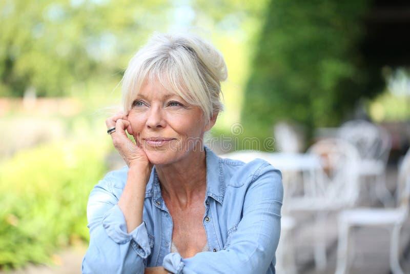 Mujer mayor sonriente en jardín fotos de archivo