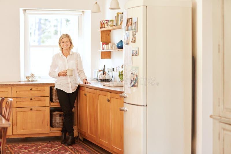 Mujer mayor sonriente en su cocina brillante y ordenada imagen de archivo