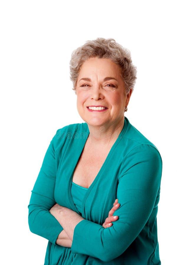 Mujer mayor sonriente feliz con los brazos cruzados foto de archivo