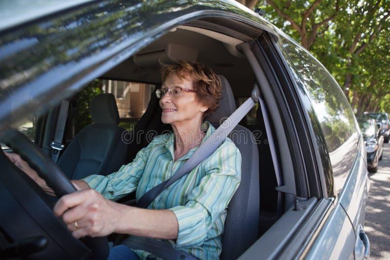 Mujer mayor sonriente que conduce el coche imagenes de archivo