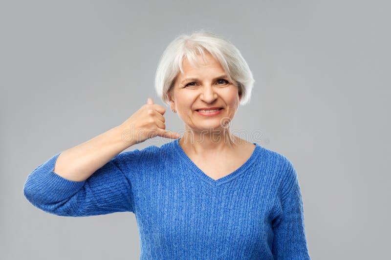 Mujer mayor sonriente que hace el teléfono que llama gesto fotos de archivo libres de regalías