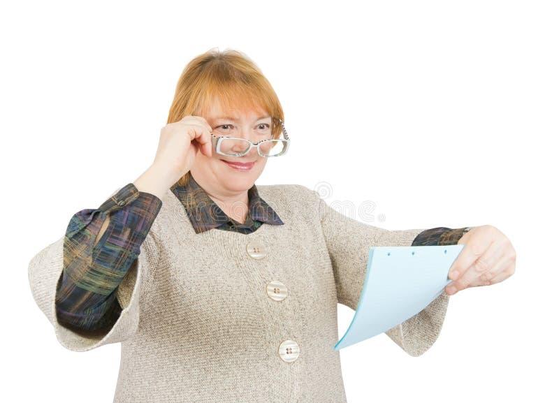 Mujer mayor sonriente que lee un papel fotos de archivo
