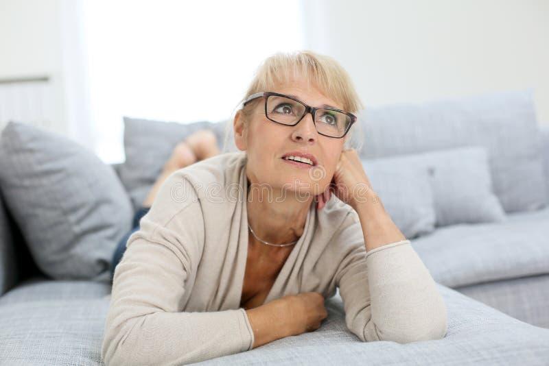 Mujer mayor sonriente que miente en el sofá fotografía de archivo libre de regalías