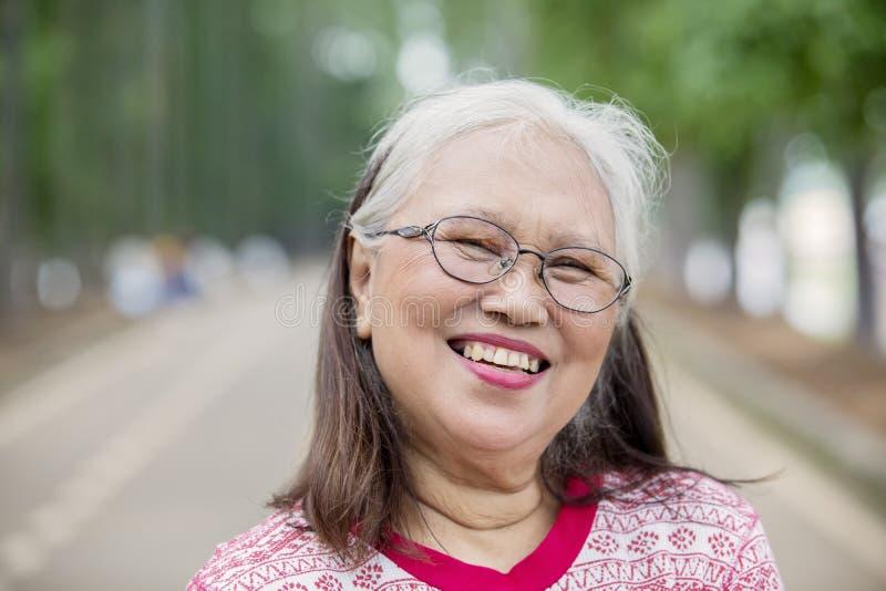 Mujer mayor sonriente que mira la c?mara foto de archivo