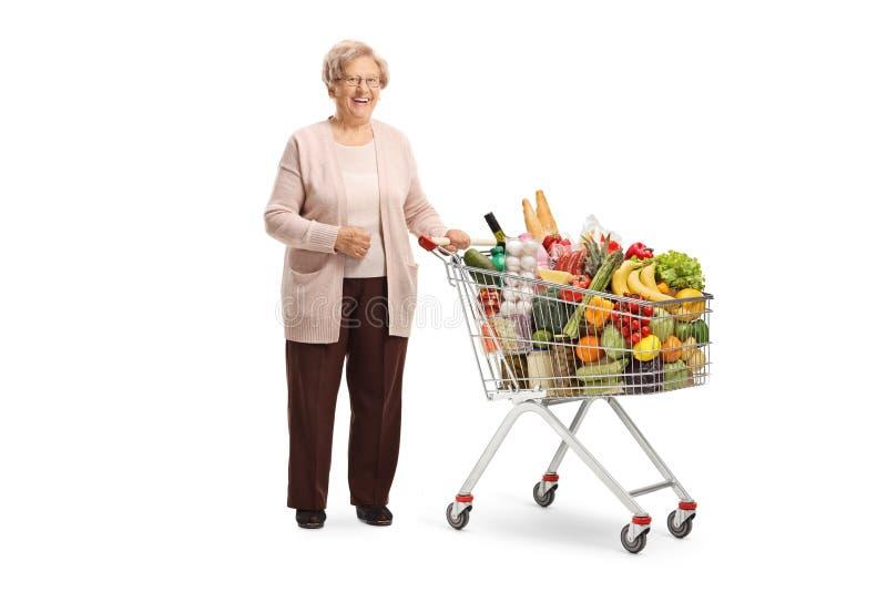Mujer mayor sonriente que presenta con un carro de la compra foto de archivo libre de regalías