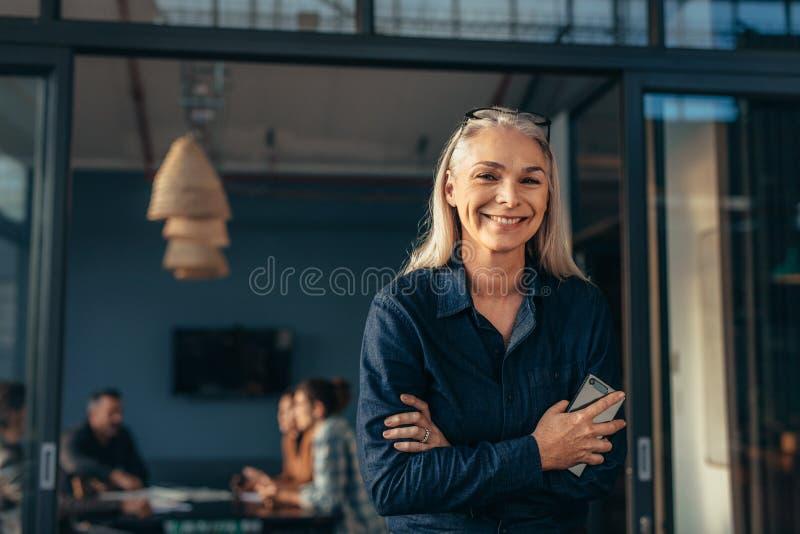 Mujer mayor sonriente que se coloca en entrada de la oficina imágenes de archivo libres de regalías