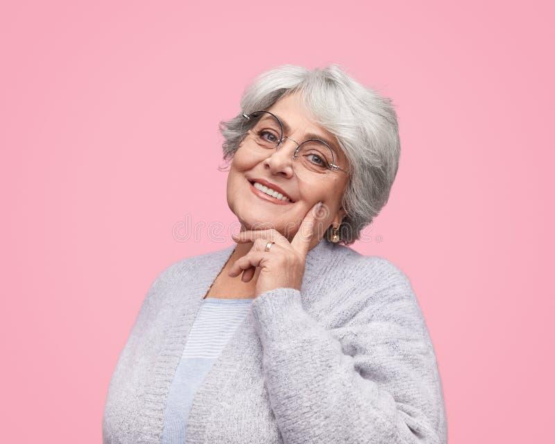 Mujer mayor sonriente que toca la mejilla imagenes de archivo