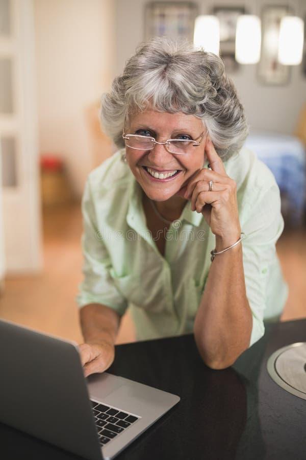 Mujer mayor sonriente que usa el ordenador portátil en casa fotos de archivo libres de regalías