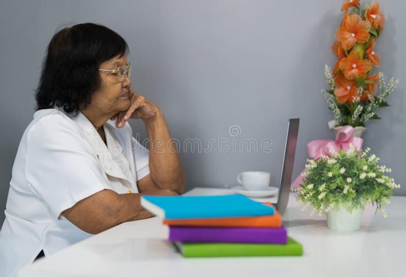 Mujer mayor subrayada que trabaja en el ordenador portátil foto de archivo libre de regalías