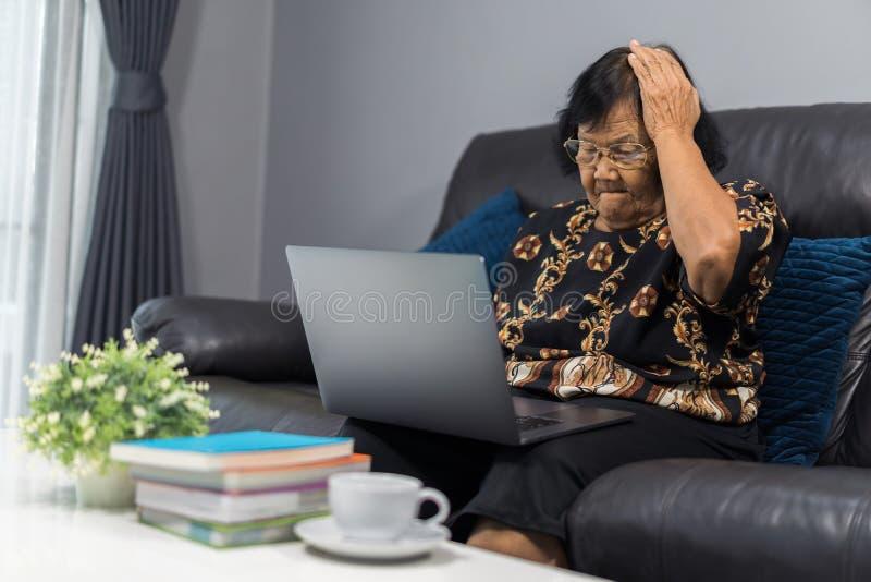 Mujer mayor subrayada que trabaja en el ordenador portátil en sala de estar fotos de archivo