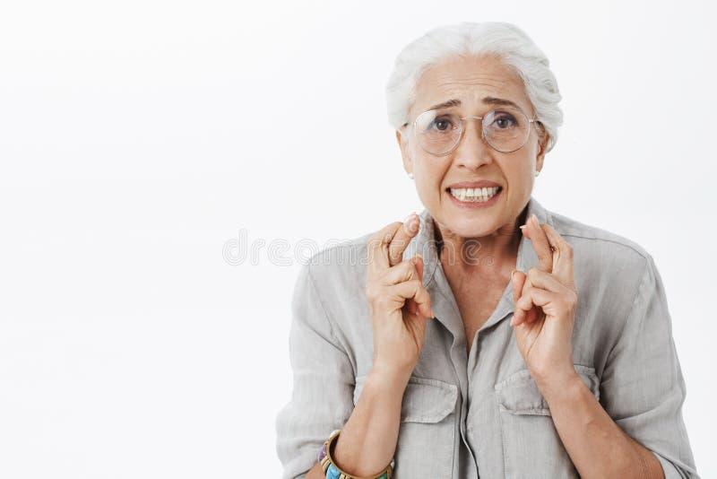 Mujer mayor tonta esperanzada ansiosa y en cuestión en vidrios con los fingeres que cruzan del pelo blanco para la buena suerte q fotografía de archivo