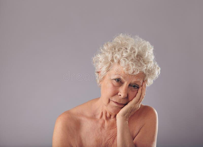 Mujer mayor trastornada en fondo gris fotografía de archivo libre de regalías