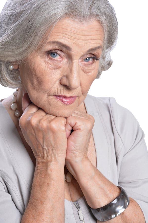 Mujer mayor triste que presenta en el fondo blanco imagen de archivo