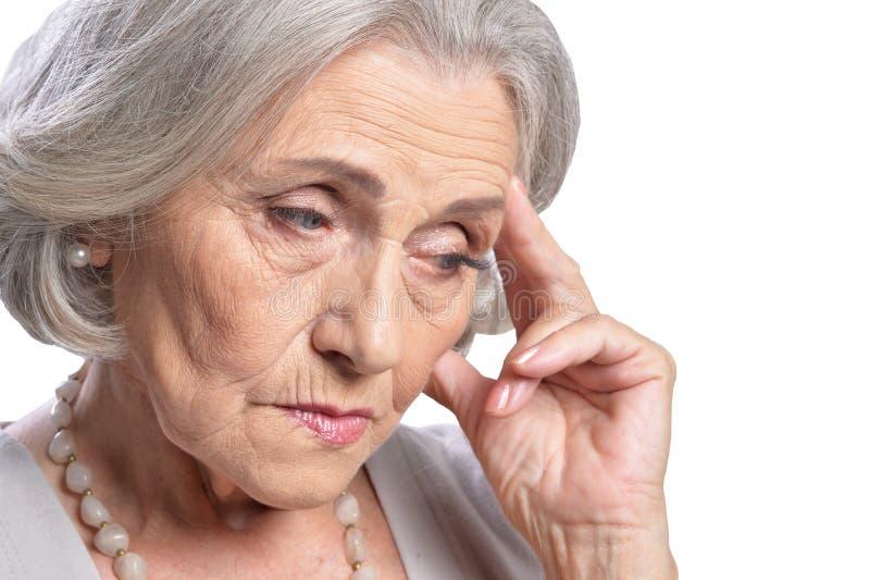 Mujer mayor triste que presenta en el fondo blanco fotos de archivo libres de regalías