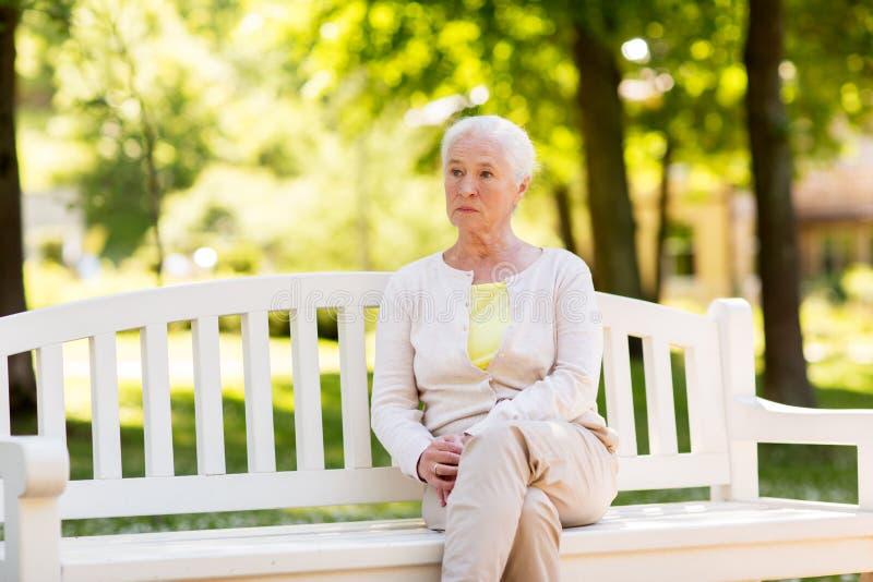 Mujer mayor triste que se sienta en banco en el parque del verano imagen de archivo libre de regalías