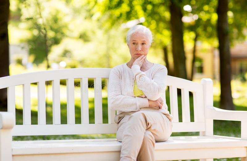 Mujer mayor triste que se sienta en banco en el parque del verano fotografía de archivo libre de regalías
