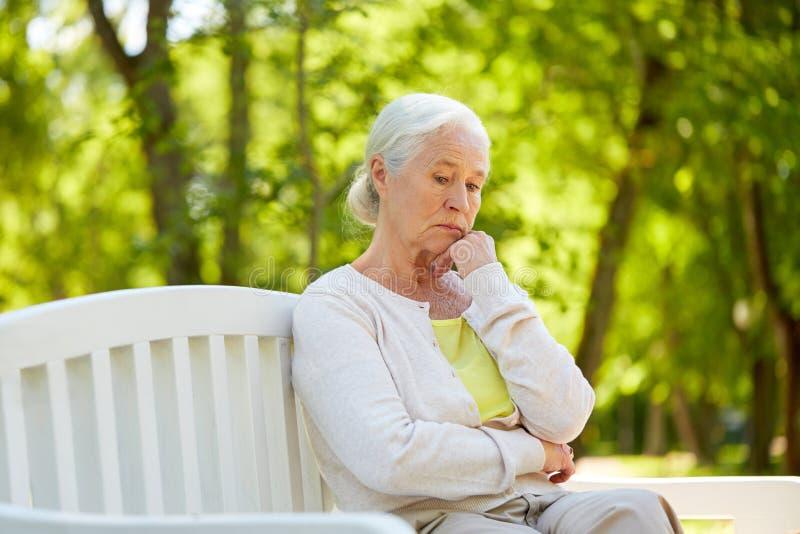 Mujer mayor triste que se sienta en banco en el parque del verano fotos de archivo libres de regalías