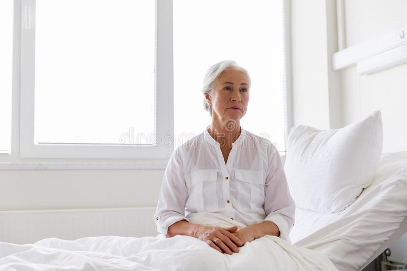 Mujer mayor triste que se sienta en cama en la sala de hospital foto de archivo libre de regalías